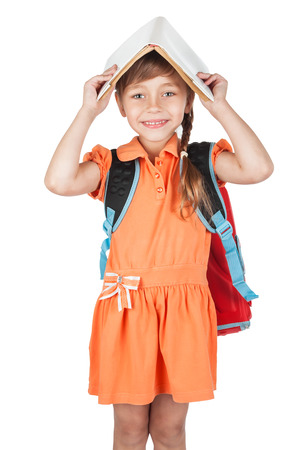 Cute schoolgirl with book on his head and a red backpack on her shoulders, isolated on white background  photo