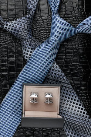 cufflink: Two necktie and  cufflinks  lying on the skin, can be used as background