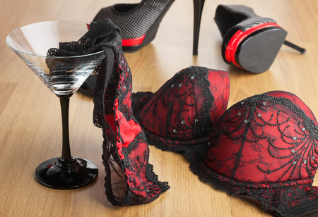 Panties in a martini glass on the background of  shoes and  bra, can be used as a background 스톡 콘텐츠