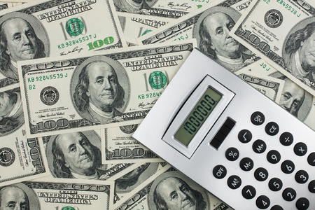 million dollars: Calculator lies on a million dollars, can be used as background Stock Photo