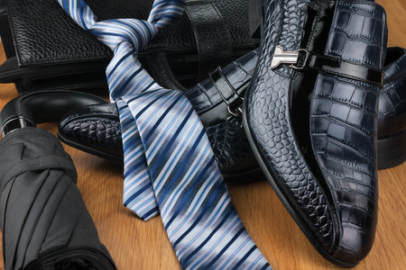 Classic mens shoes, tie, umbrella and bag on the wooden floor, can be used as background