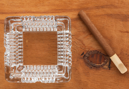 Glass ashtray with cigar  on a wooden surface, can be used as background photo