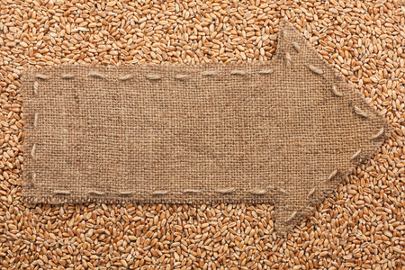 Pointer of burlap with place for your text, lying on a wheat background photo
