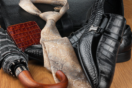 Classic mens shoes, tie, umbrella,wallet  and bag on the wooden floor, can be used as background Stock Photo