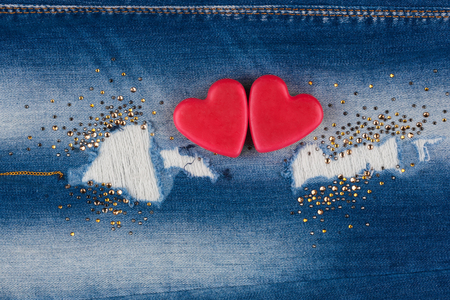 The concept of two lovers hearts lying on the jeans, with place for your text photo