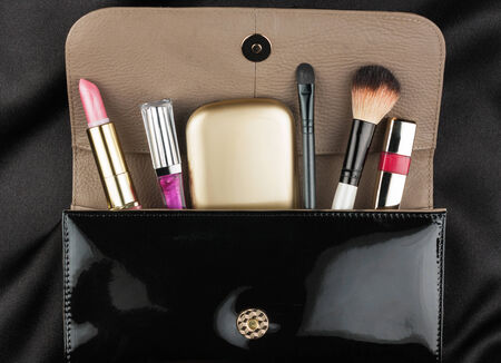 Black patent leather bag  with cosmetics, on black background Stock Photo