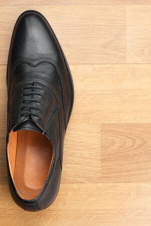Classic mens shoes stand on the wooden floor, with place for your text photo