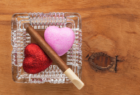 harmful: Love and harmful habit in a glass ashtray, conceptual image