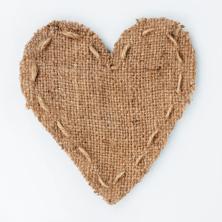burlap sack: Symbolic heart of burlap lies on a white background, with place for your text
