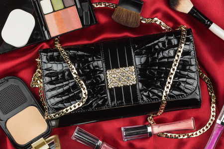 patent leather: Beautiful bag from patent leather and cosmetics lying on red satin, as background
