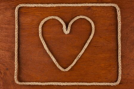 cable stitch: Heart made of rope on a wooden surface, conceptual image