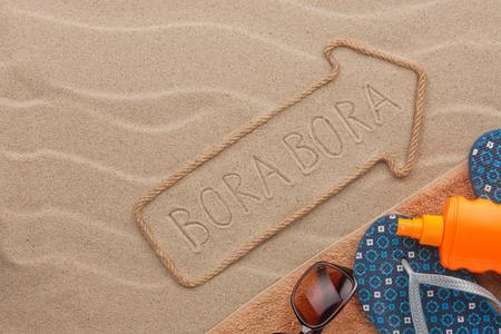 bora: Bora Bora  pointer and beach accessories lying on the sand, as background