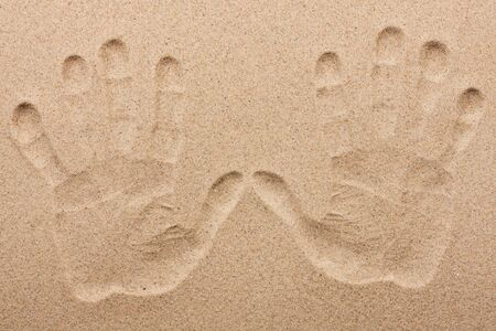 indentation: Imprint of two human hands in the sand, as background