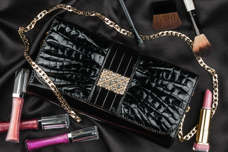 patent leather: Beautiful bag from patent leather and cosmetics lying on black satin, as background