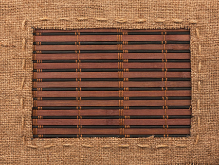 Frame of burlap, lies on a bamboo mat, with place for your text photo
