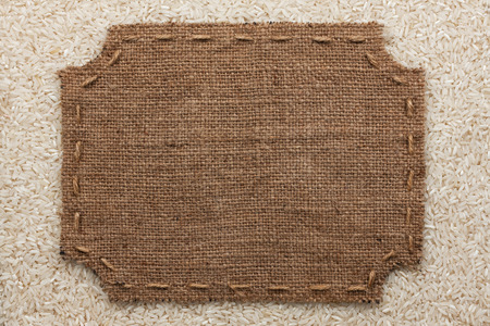 stitches: Figured frame with burlap and stitches with  place for your text lying on rice  grains as a background Stock Photo