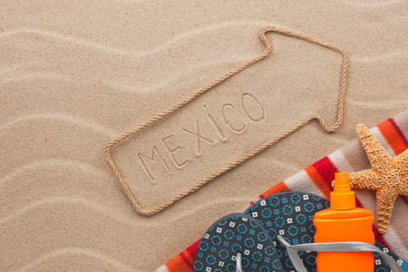 Mexico pointer and beach accessories lying on the sand, as background photo
