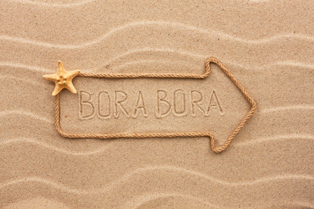 bora: Arrow made of rope and sea shells with the word Bora Bora on the sand, as background
