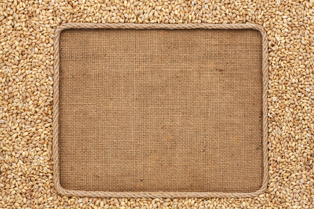 Barley: Frame made of rope with pearl barley grains on sackcloth Stock Photo