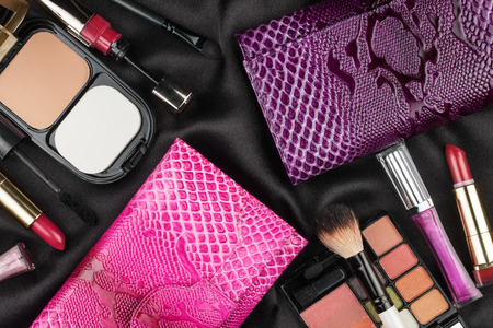 Beautiful pink and lilac bags among cosmetics, as background