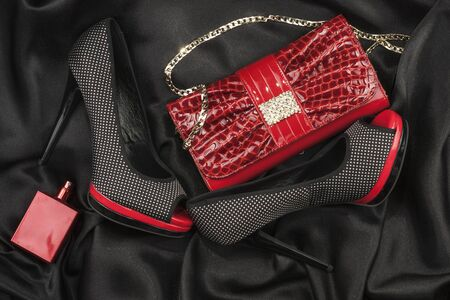 black satin: Red bag, shoes and perfume lying on black satin as background