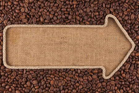 Pointer made from rope with  coffee beans  lying on sackcloth, with space for your text photo