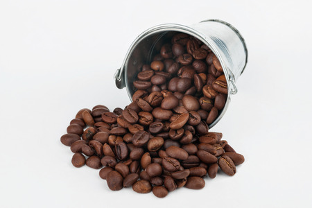 spilling: Coffee beans spilling out of bucket, on a white background