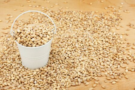 pearl barley: White bucket with pearl barley on the wooden floor, as a background Stock Photo