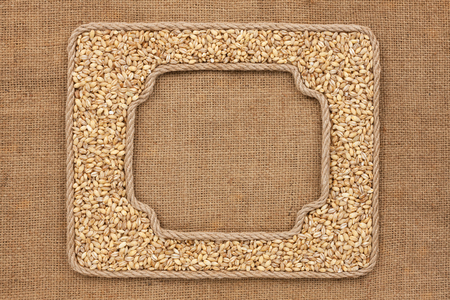pearl barley: Two frames made of rope with pearl barley grains on sackcloth, as background, texture