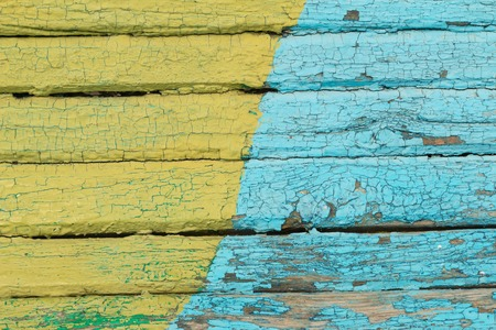 color: Vintage wood background with peeling  yellow and blue paint.texture Stock Photo