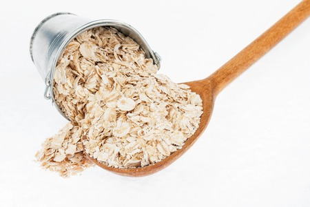 avena en hojuelas: Bucket of rolled oats crumbles in the a wooden spoon, on a white background