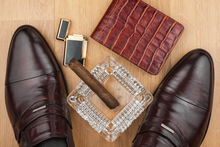 Male still life, classic mens shoes and a cigar in an ashtray, can use as background Stock Photo