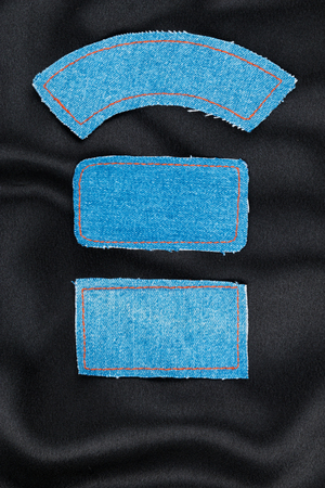 inner wear: Labels made of jeans lying on the black silk, as background Stock Photo