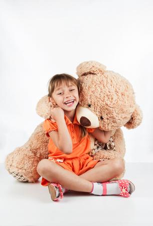 petite fille avec robe: Petite fille jouant avec un ours en peluche, sur un fond blanc Banque d'images
