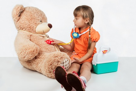 Baby is playing doctor, treats a bear, on white background