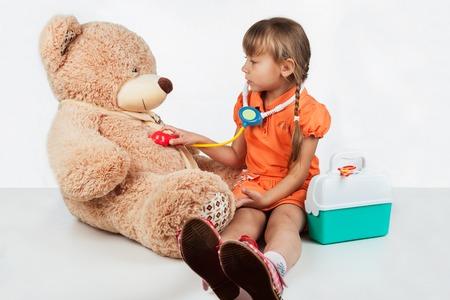Baby spielt Arzt, behandelt einen Bären, auf weißem Hintergrund Standard-Bild - 48429872