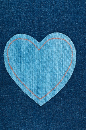 symbolic: Symbolic heart made of jeans lying on dark jeans, with space for your text Stock Photo