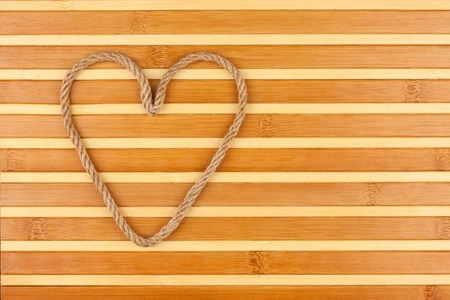 symbolic: Symbolic heart made of rope lying on a bamboo mat, as background