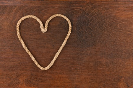 symbolic: Symbolic heart made of rope lying on a wooden surface , as background Stock Photo