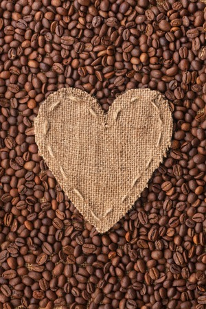 sackcloth: Frame in the shape of heart made of burlap with coffee beans, with space for your text