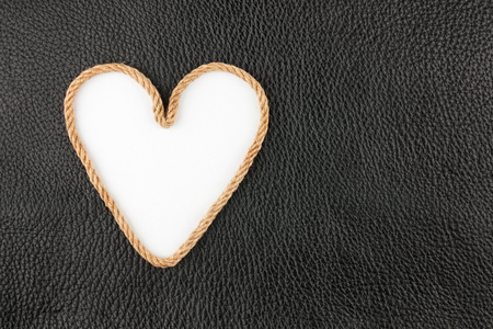 symbolic: Symbolic heart made of rope lying on a natural leather , as background Stock Photo