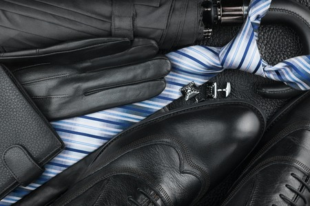 cufflinks: Classic mens shoes, tie, cufflinks, gloves, umbrella on natural skin, can be used as background