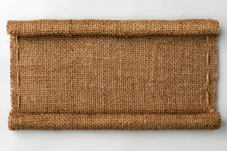 gunny: Frame of burlap with curled edges in the form of a scroll, lies on a white background, can be used as texture Stock Photo