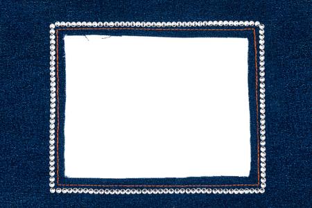 mezclilla: Marco de mezclilla con jeans oscuros con diamantes de imitación de plata, aislado en un fondo blanco Foto de archivo