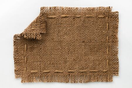 furled: Frame of burlap with curled edges, lies on a white background, can be used as texture