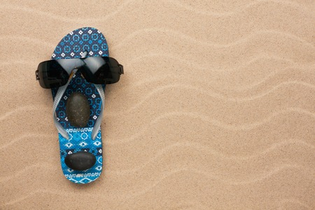 flipflops: Concept of a mans face, flip-flops and sunglasses on wavy in sand