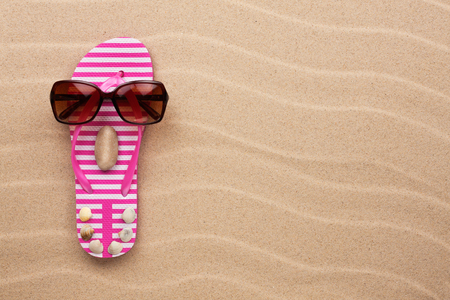 flipflops: Concept of a womans face, flip-flops and sunglasses on wavy in sand
