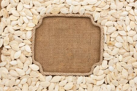Figured frame made of rope with pumpkin seeds on sackcloth, with place for your creativity