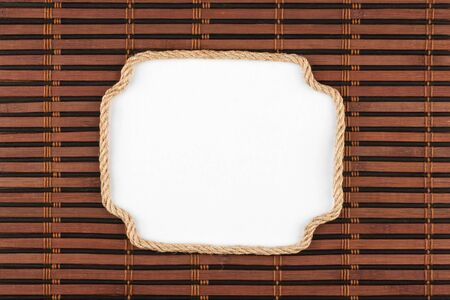 cable stitch: Frame of rope lying on a bamboo mat with a white background  for your text, view from above