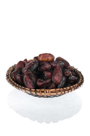 heaped: Dried date  on the plate  isolated on a white background Stock Photo
